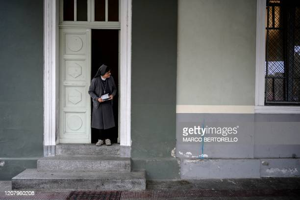A nun stands at the entrance of the Chapel of the San Giovanni Bosco Oratory on March 22 2020 in Saluzzo near Cuneo Northwestern Italy Priests and...
