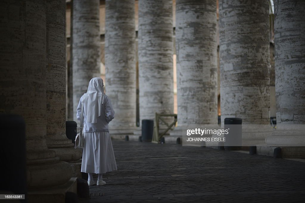A nun stands in the Colonnade at the St Peter's square on the first day of the conclave on March 12, 2013 at the Vatican. Cardinals moved into the Vatican today as the suspense mounted ahead of a secret papal election with no clear frontrunner to steer the Catholic world through troubled waters after Benedict XVI's historic resignation. The 115 cardinal electors who pick the next leader of 1.2 billion Catholics in a conclave in the Sistine Chapel will live inside the Vatican walls completely cut off from the outside world until they have made their choice.