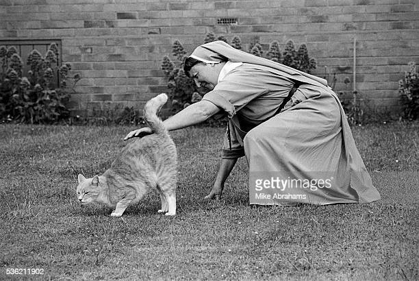 Nun stroking a cat at the Anglican Convent of the Holy Name Malvern