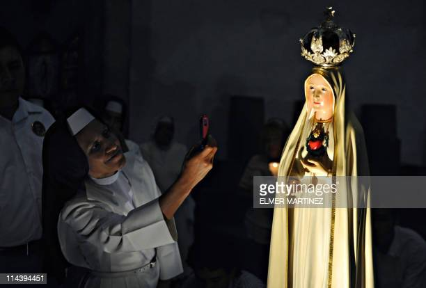 A nun takes a picture with her mobile phone of a statue of Our Lady of Fatima during a mass at the Managua Cathedral late on May 13 2011 Hundreds of...