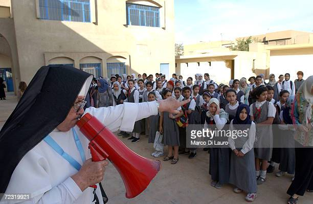 A nun uses a megaphone to speak to Iraqi students on the first day back to a Christian school May 3 2003 in Baghdad Iraq Approximately 120 female...