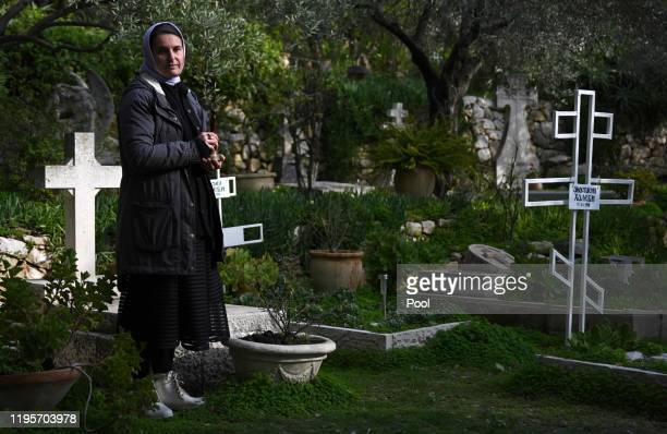 A nun waits to ring a bell to announce the arrival of Prince Charles Prince of Wales at the Church of St Mary Magdalene at the Mount of Olives on...