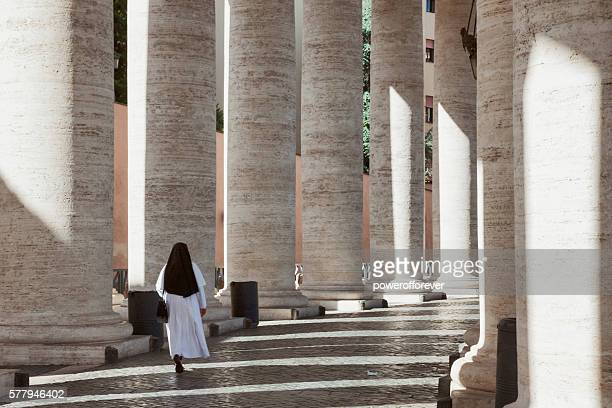 Nun walking among Bernini's Colonnade in St. Peter's Square, Vatican