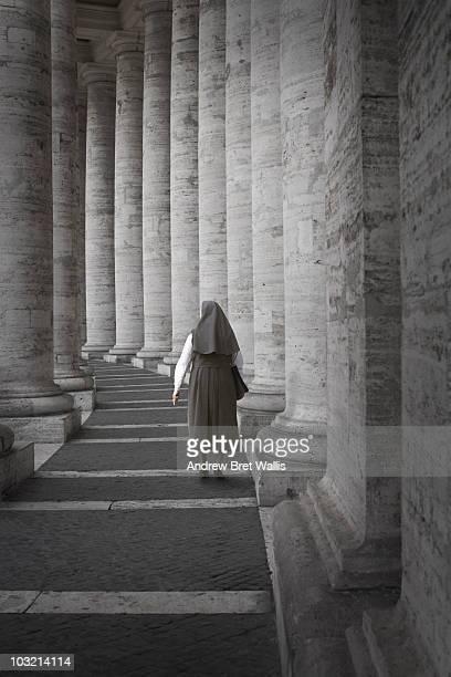 Nun walking away down St Peter's Colonnade in Rome