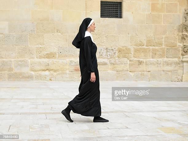Nun walking in front of stone wall, Alicante, Spain,