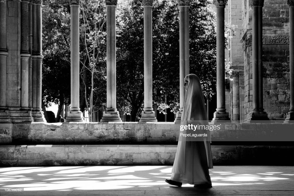 Nun Walking Through Church Cloister, Black and White : Stock Photo