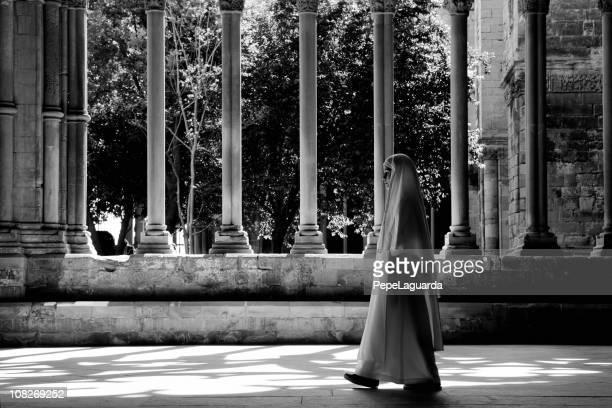 nun walking through church cloister, black and white - nun stock photos and pictures