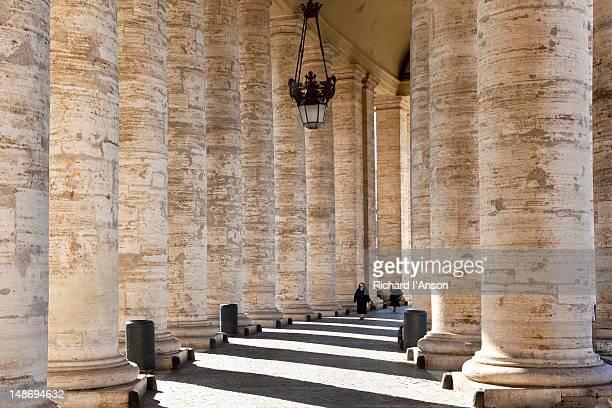 nun walking through colonnade on piazza san pietro. - nun stock-fotos und bilder