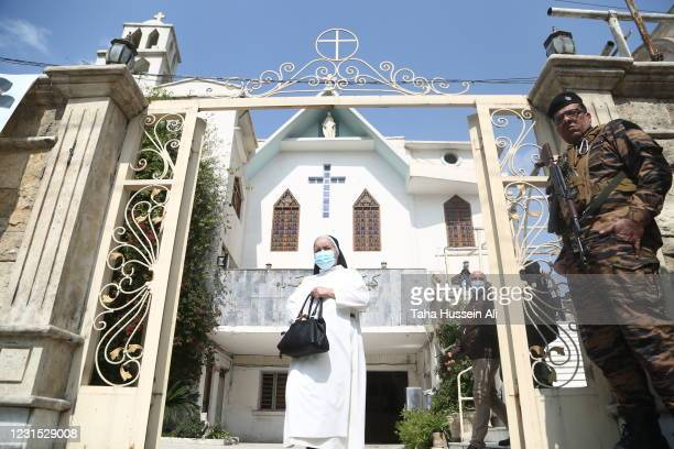 Nun walks outside the Mother Mary's Chaldean Catholic Church as she heads to the airport to wait for the arrival of Pope Francis on March 5, 2021 in...