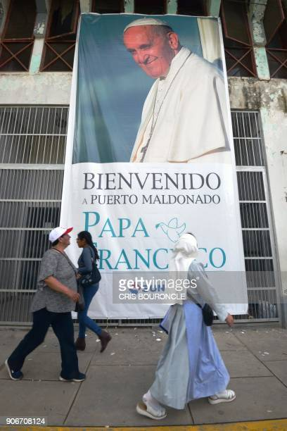 A nun walks past a banner welcoming Pope Francis in the town of Puerto Maldonado in Peru's Amazonian region on January 18 2018 Pope Francis headed...