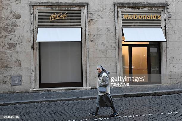TOPSHOT A nun walks past a newlyopened McDonald's restaurant near the Vatican on January 3 2017 in Rome The US fastfood chain opened a restaurant in...