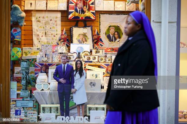 A nun walks past a shop selling souvenirs of Britain's Prince Harry and his fiance US actress Meghan Markle on May 2 2018 in Windsor England St...