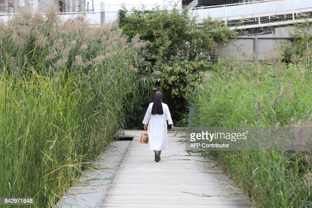A nun walks through the Martin LutherKing garden in the Batignolles area on September 5 2017 in Paris / AFP PHOTO / LUDOVIC MARIN