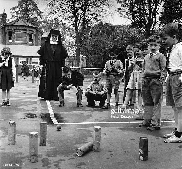 A nun watches the students play a ball game at the Saint Louis Convent School in Newmarket England