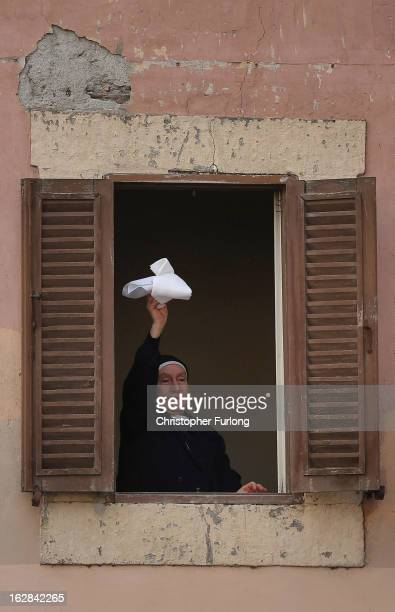 A nun waves her handkerchief as she waits for Pope Benedict XVI to address pilgrims for the last time as head of the Catholic Church from the window...