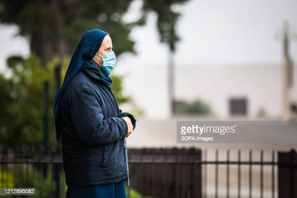 Nun wearing a face mask as a precaution, attends mass at a distance during the apparition of Our Lady of Fatima. Due to the COVID-19 pandemic, this...