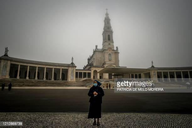 Nun wearing a face mask attends a ceremony marking the 103rd anniversary of the apparitions of Our Lady Fatima at the Fatima shrine in central...