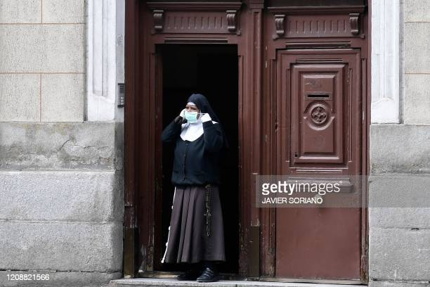 A nun wearing a face mask stands at the entrance of Inmaculada and San Pascual monastry in Madrid on April 1 during a national lockdown to prevent...