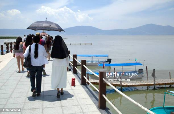 nun wearing habit walks along a dock under an umbrella; chapala, jalisco, mexico - timothy hearsum stock pictures, royalty-free photos & images