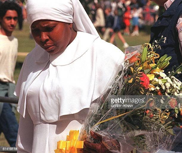 A nun with a bouquet of flowers adds to the mountain already growing outside Diana Princess of Wales' former residence at Kensington Palace London 02...
