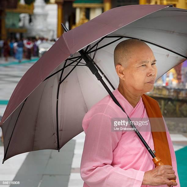 A nun with a parasol walks through the Shwedagon Pagoda in Yangon on June 16 2016 in Yangon Myanmar