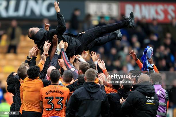 Nuno Espirito Santo manager of Wolverhampton Wanderers is thrown into the air by his players as they celebrate promotion during the Sky Bet...