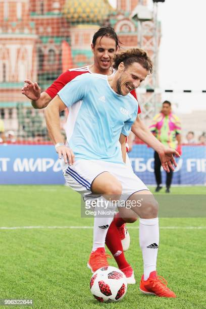 Nuno Gomes competes with Diego Forlan during the Legends Football Match in 'The park of Soccer and rest' at Red Square on July 11 2018 in Moscow...