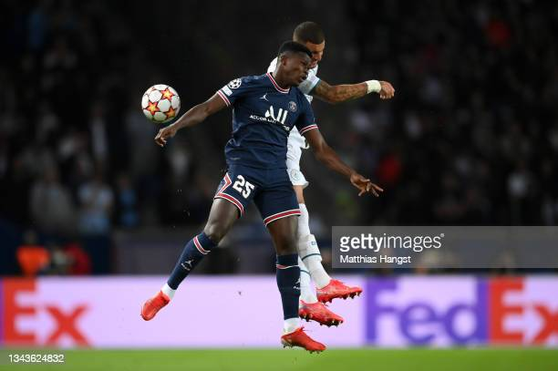 Nuno Mendes of Paris Saint-Germain competes for a header with Kyle Walker of Manchester City during the UEFA Champions League group A match between...
