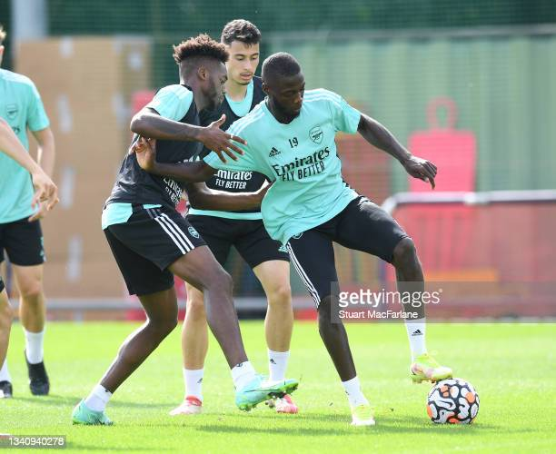 Nuno Tavares and Nicolas Pepe of Arsenal during a training session at London Colney on September 17, 2021 in St Albans, England.