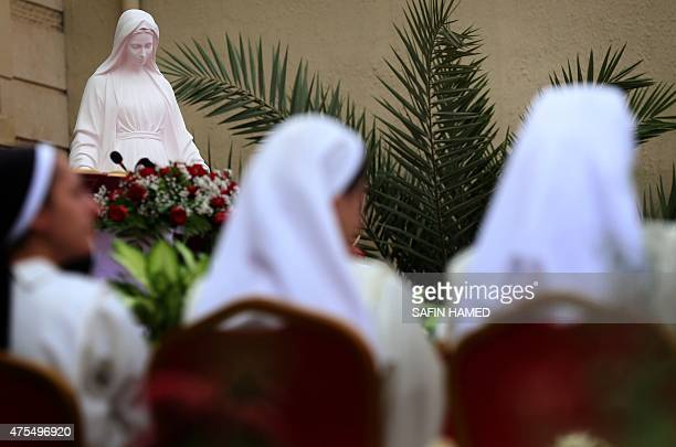 Nuns along with Iraqi Christians who fled the violence in the northern Iraqi city of Mosul attend a mass celebrating the coronation of the Virgin...