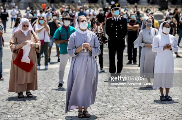 Nuns and Faithfuls attend the Regina Caeli Sunday prayer in the reopened St Peter's Square at the Vatican on May 24 2020 in Rome Italy Pope Francis...