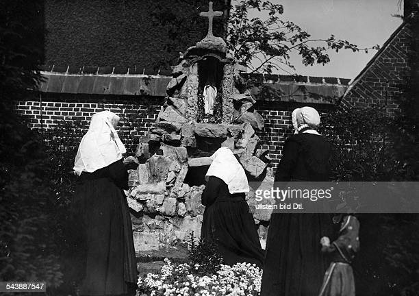 nuns Beguines nuns during the prayer in the cloistered courtyard in front of the Grotte de Lourdes undated Photographer Frankl Vintage property of...