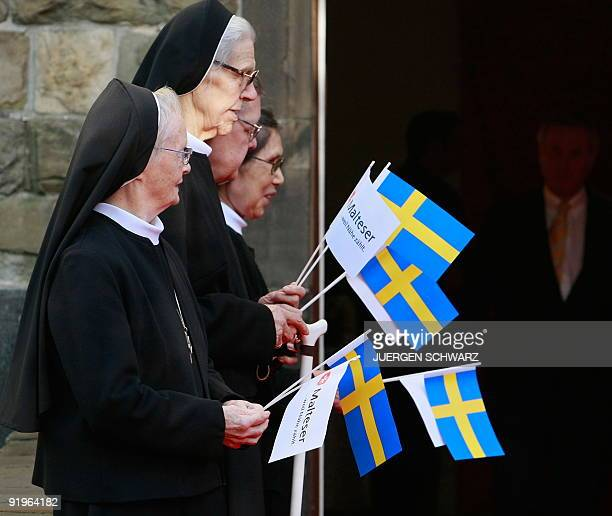 Nuns carring Swedish flags arrive to greet Queen Silvia of Sweden at the opening ceremony of the St Hildegardis dementia hospital in the western...