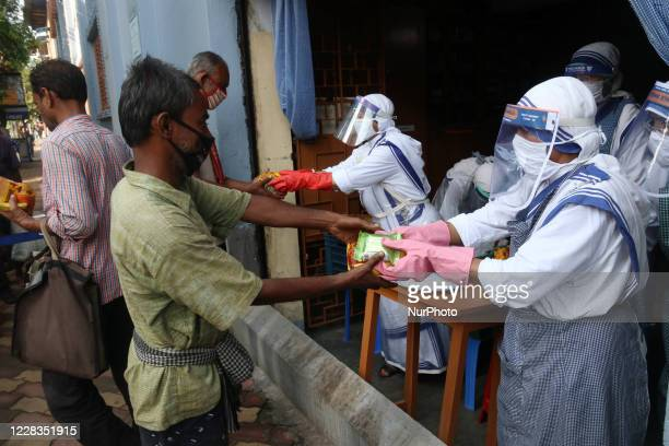 Nun's from the Catholic Order of the Missionaries of Charity wearing a facemask and shield distributes food packets and tea to underprivileged people...