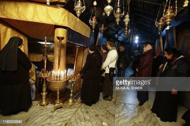Nuns join worshippers in prayer at the Church of the Nativity, in Bethlehem in the Israeli-occupied West Bank on January 6 as some Orthodox...