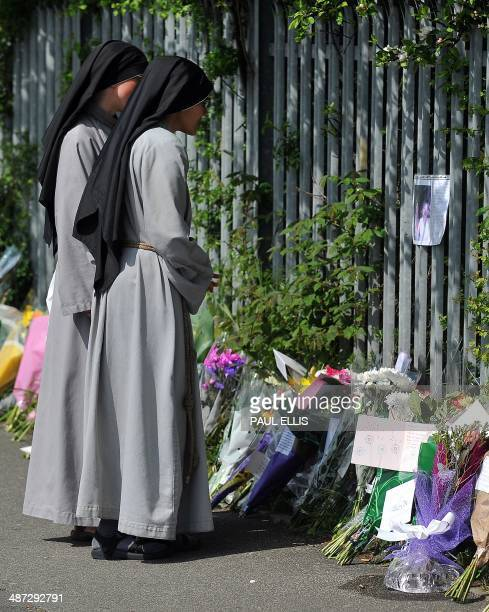 Nuns look at floral and written tributes to murdered teacher Anne Maguire outside Corpus Christi Catholic College in Leeds, northern england, on...