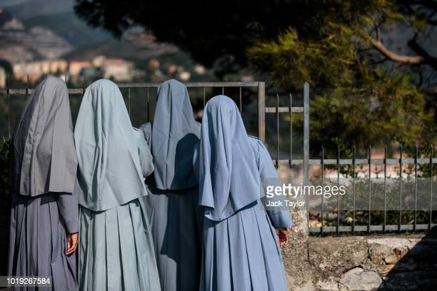 Nuns look at the wreckage of the Morandi Bridge from a high vantage point days after a section of it collapsed on August 19 2018 in Genoa Italy 43...