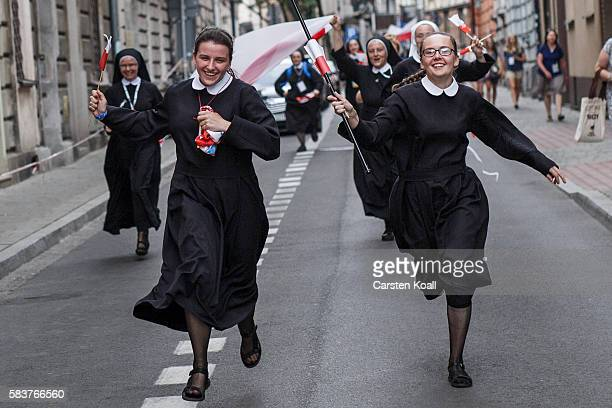 Nuns running along the street to see the passing Pope Francis on July 27 2016 in the old town city center in Krakow Poland Almost two million young...