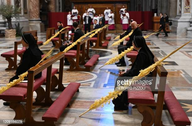 Nuns sit by palm branches as they wait for the start of the Pope's Palm Sunday Mass behind closed doors in St Peter's Basilica mass on April 5 2020...