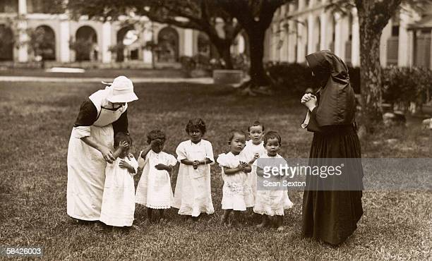 Nuns teach the children to pray at an orphanage run by the Dames de Saint-Maur in Johor, Malaysia, circa 1930.