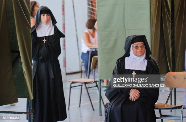 Nuns wait to cast their vote during the presidential runoff election in Santiago Chile on December 17 2017 Chileans started to vote in a presidential...