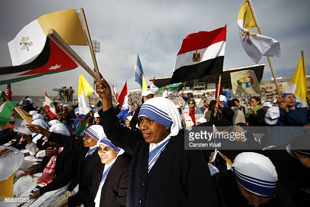 Nuns wave flags to welcome Pope Benedict XVI as he celebrates a mass in the openair international stadium on May 10 2009 in Amman Jordan Pope...