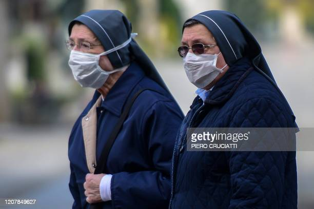 Nuns wearing a face mask stand inside the closed Monumental Cemetery of Bergamo Lombardy on March 20 2020 during the country's lockdown aimed at...
