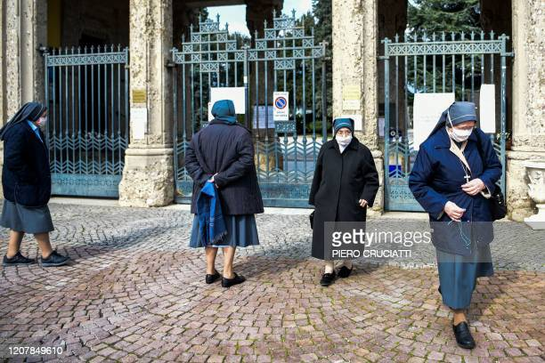Nuns wearing a face mask wait outside the closed Monumental Cemetery of Bergamo Lombardy on March 20 2020 during the country's lockdown aimed at...