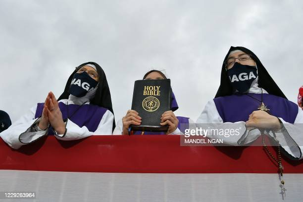 Nuns wearing masks displaying Trump's MAGA slogan listen as US President Donald Trump speaks during a campaign rally at Pickaway Agriculture and...