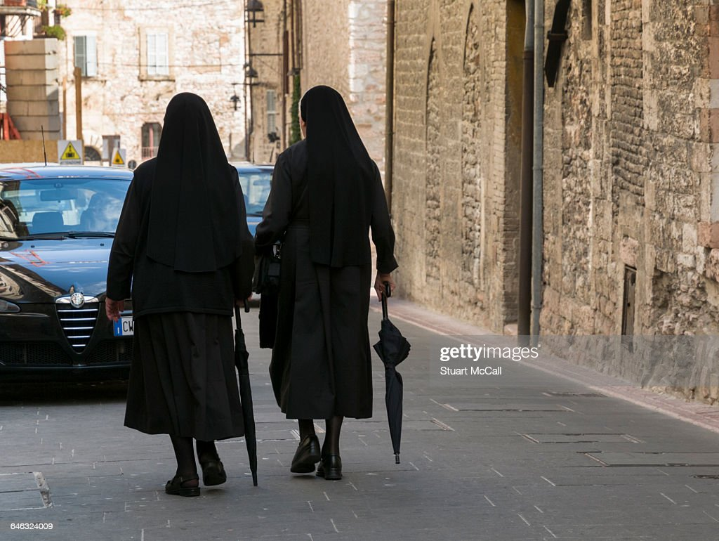 Nuns with umbrellas walking against traffic. : Stock Photo