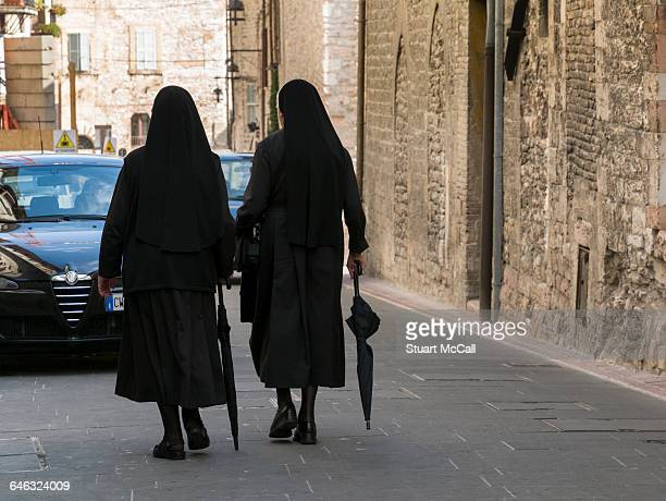 nuns with umbrellas walking against traffic. - nun stock photos and pictures
