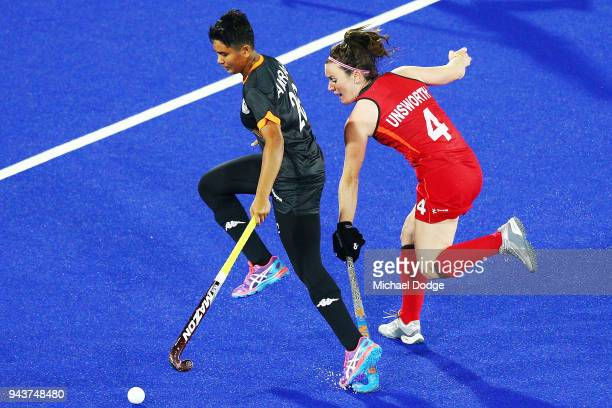 Nuramirah Zulkifli of Malaysia and Laura Unsworth compete for the ball during Hockey on day five of the Gold Coast 2018 Commonwealth Games at Gold...