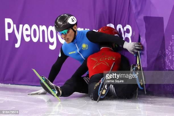 Nurbergen Zhumagaziyev of Kazakhstan and Hongzhi Xu of China crash during the Men's 1500m Short Track Speed Skating qualifying on day one of the...