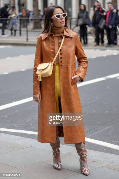 Nurce Erben wearing orange trench coat sunglasses and yellow trousers during London Fashion Week February 2020 on February 14 2020 in London England